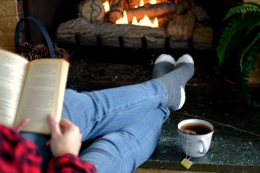 Woman sitting by a cozy fireplace fire reading a book with a hot cup of tea.